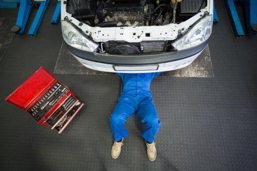 meccanico sdraiato che controlla il sotto di una macchina
