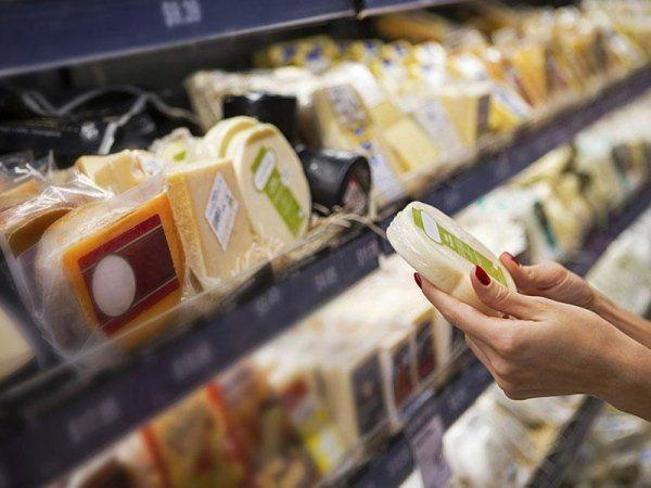 una donna con in mano una confezione di un formaggio e dietro, sullo scaffale altri formaggi esposti