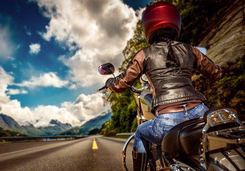 donna guida una motocicletta su strada