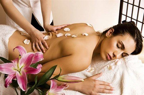 donna sdraiata di schiena mentre una massaggiatrice le massaggia la schiena con dei petali