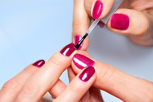 una mano che applica uno smalto violetto sulle unghie