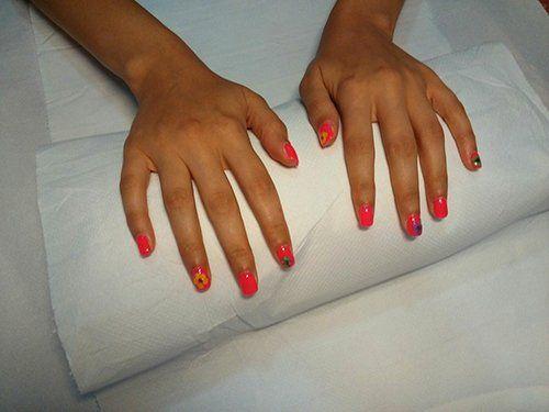 due mani con unghie dipinte di rosso e decorate a motivi floreali