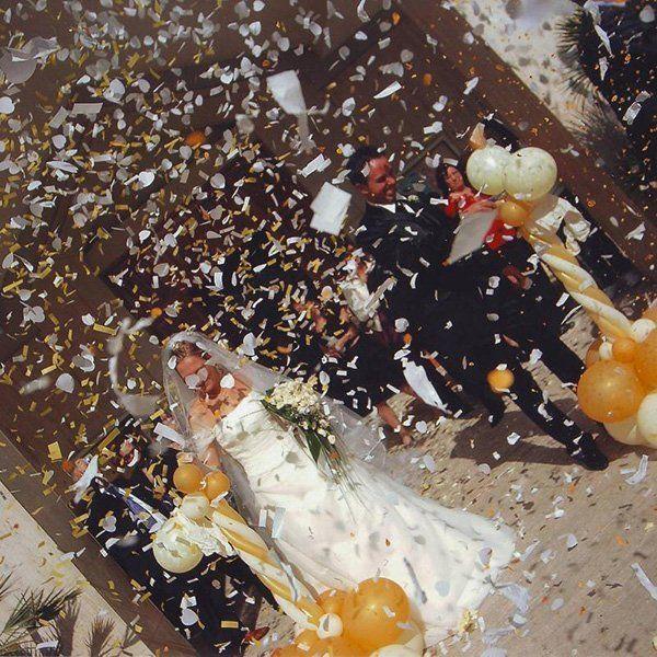 una sposa e uno sposo che escono dalla chiesa con coriandoli e palloncini