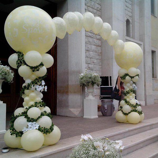 arco davanti a una casa realizzato con palloncini e fiori binachi