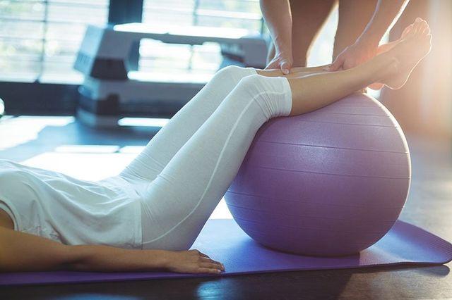 una donna sdraiata con i piedi su una palla medica  e un fisioterapista che le sorregge i piedi