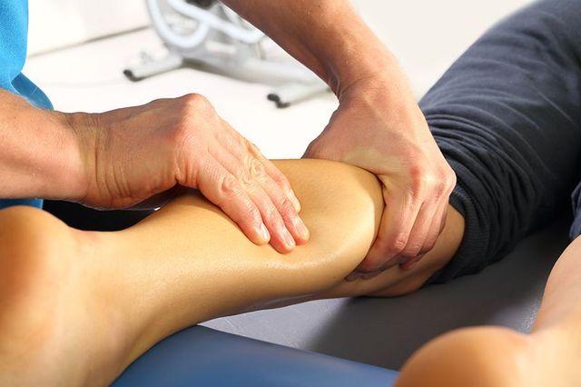 vista da vicino di un massaggiatore mentre massaggia il polpaccio di una donna a Catania