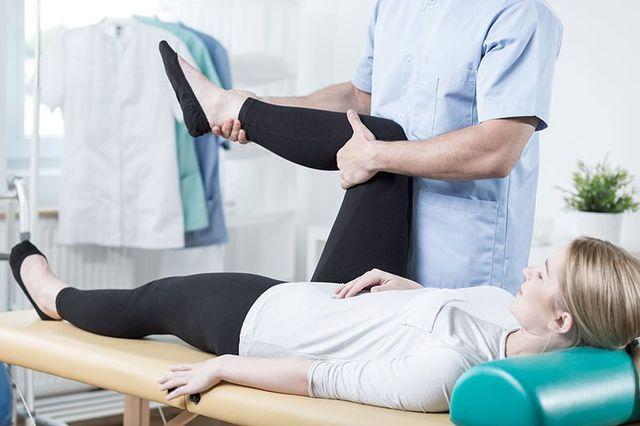 una donna con i capelli biondi sdraiata con la gamba destra alzata e un fisioterapista mentre gliela sorregge a Catania