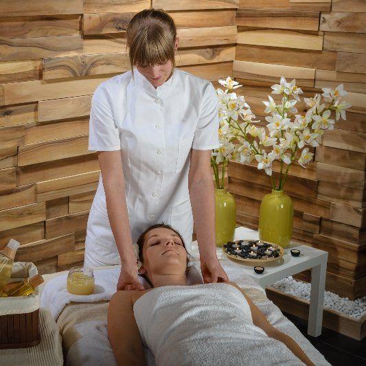 A woman massages the shoulders of a client