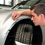 un meccanico controlla la carrozzeria di un'auto