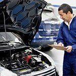 meccanico mentre controlla il motore di un'auto
