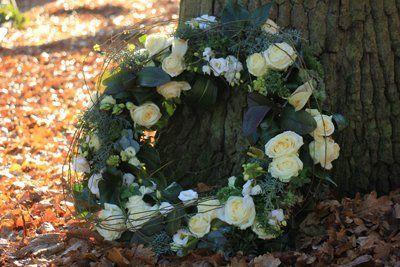 corona di fiori appoggiata su un tronco d'albero