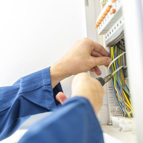 due mani che sistemano dei cavi gialli e azzurri in un quadro elettrico