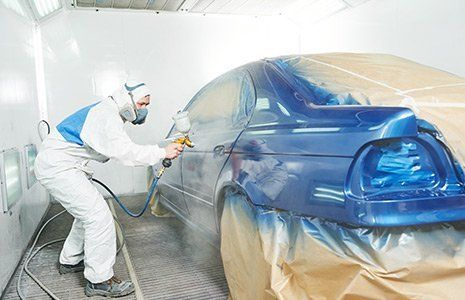 Employee painting car body in Rochester