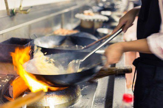 Cuoco cucinando il cibo nella cucina del Ristorante 168 WOK a Palermo
