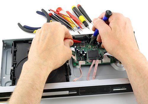 due mani che riparano un lettore DVD