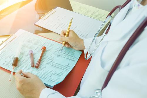 medico scrive su dei documenti tenendo delle provette sulla scrivania