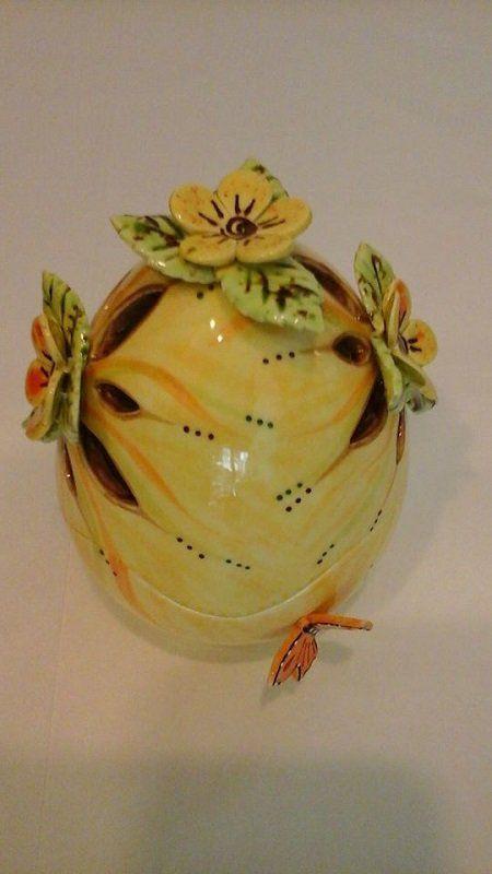una creazione ovale in ceramica di color giallo con dei fiori ai lati