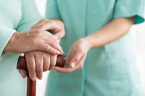 Persona anziana cammina assistita usando un bastone a Torre de' Negri