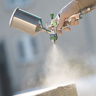 A silver paint sprayer being used on a wood surface