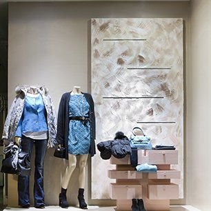 A silver spray painted panel on a wall in a clothes shop, with two mannequins and display shelves in front of it
