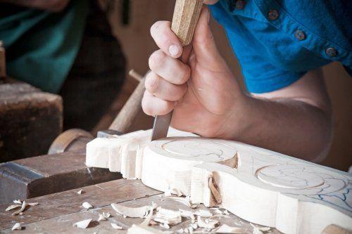 un artigiano mentre lavora con legno e un scalpello