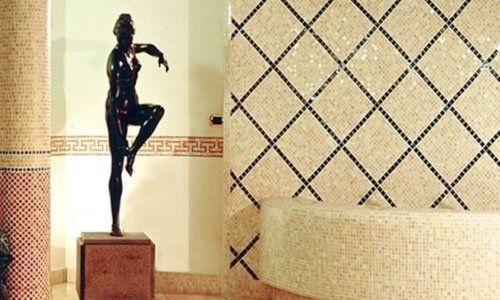 una statua nera di una donna in posa e dei muri piastrellati a mosaico di color beige a linee nere