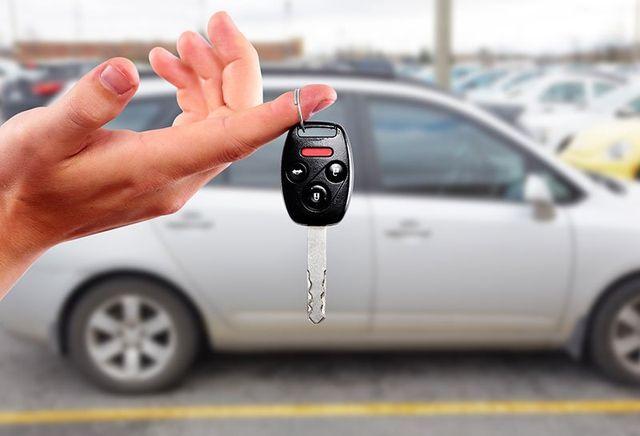 una mano con in mano una chiave di una vettura  monovolume grigia