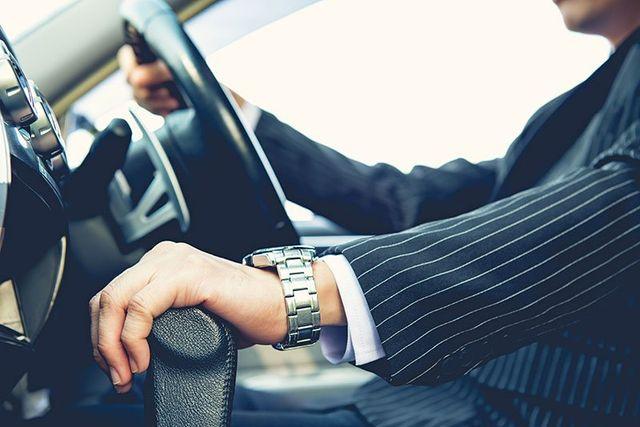 un uomo con un completo gessato in una macchina e la visuale e' focalizzata sulla sua mano appoggiata sul cambio e con un orologio al polso