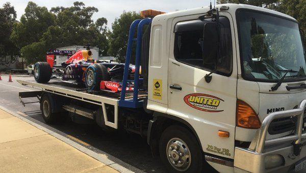 Tilt tray truck carrying formula one car