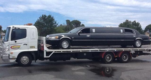 tilt tray truck towing a limousine