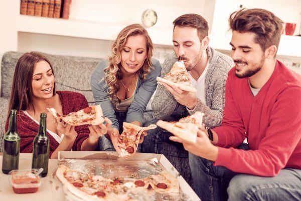 Quattro persone condividendo una pizza e delle birre