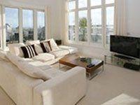 Salon con sofà chiari, television e due grandi finestre di PVC bianco