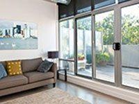 Grande porta scorrevole di terrazza in PVC grigio e bianco, sofà marrone