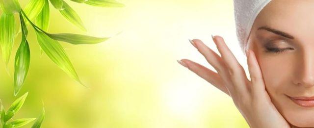una donna con un asciugmano in testa mentre si accarezza il viso  e sulla sinistra delle foglie