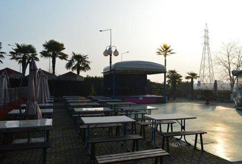 Dei tavoli con delle panche e vista delle palme