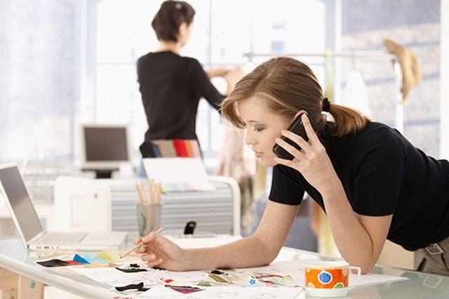 Junge Frau spricht am Telefon, macht sich gleichzeitig Notizen.