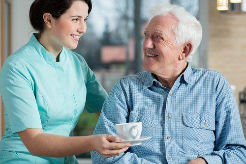 ELSNER Pflegekraft reicht einem Herren eine Tasse Kaffee