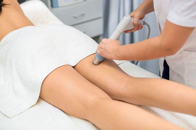una specialista mentre pratica con un apparecchio un massaggio anti cellulite ad una donna draiata a pancia in giu su un lettino a Nocera Inferiore, SA