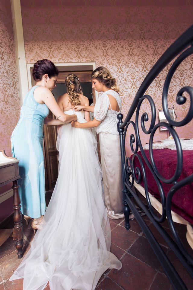 vista di una sposa dal dietro che indossa un abito bianco di pizzo mentre scende le scale a Imola, BO