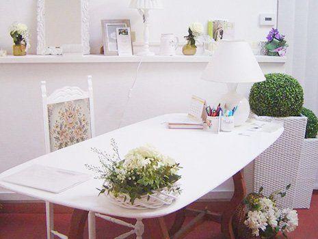 Stanza con un tavolo bianco con una lampada, diversi fiori e piante all'interno a Imola, BO