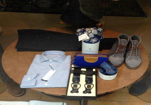 un tavolino con una camicia,un paio di pantaloni, delle bretelle e un paio di scarpe da uomo