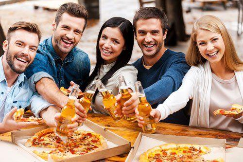 gruppo di amici che mangiano pizza e bevono birra