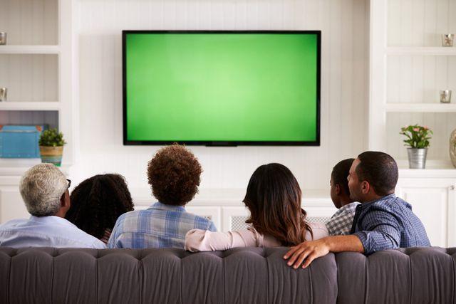 persone che guardano la televisione con uno schermo verde