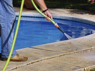 particolare di un tubo dell'acqua che pulisce un bordo piscina