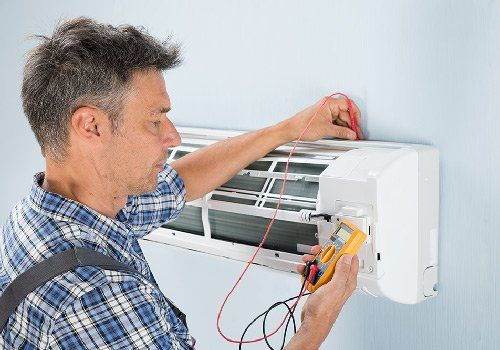 Man performing air conditioning repairs in a Penrith home