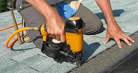 Carpenter using a nail gun to attach asphalt shingles to roof