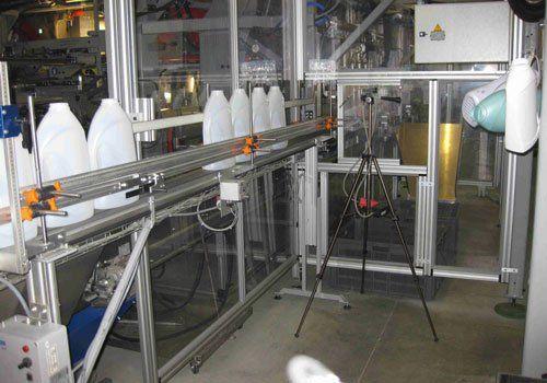 postazione cabinata in vetro con catena di montaggio e una serie di caraffe in plastica una vicino all'altra