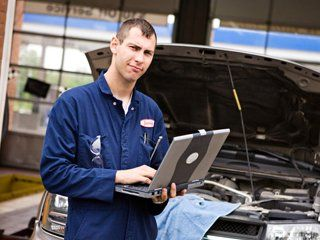 A man with a garage working on a lap top