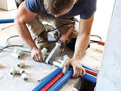 Un uomo che installa un imnpianto di riscaldamento a terra