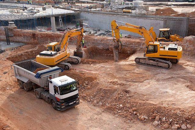 un cantiere con un camion e due scavatrici